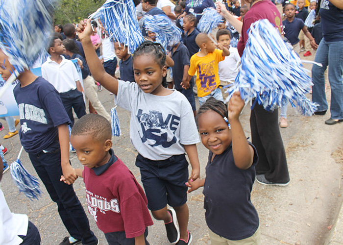 Elementary students with pom poms marching in parade