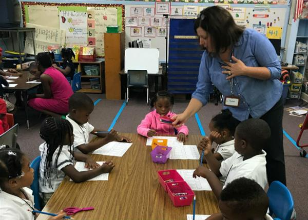 A kindergarten teacher works with students seated at a table.