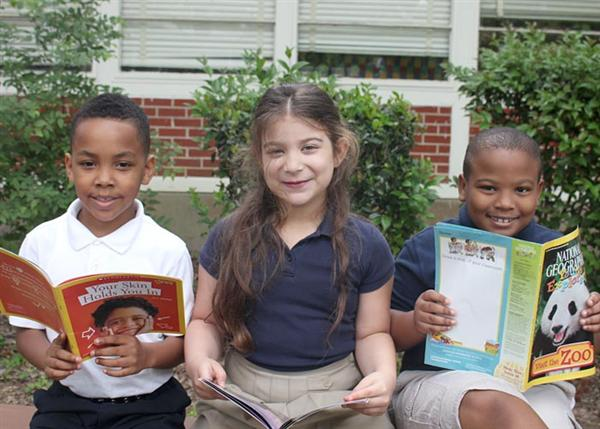 Third grade students reading and smiling
