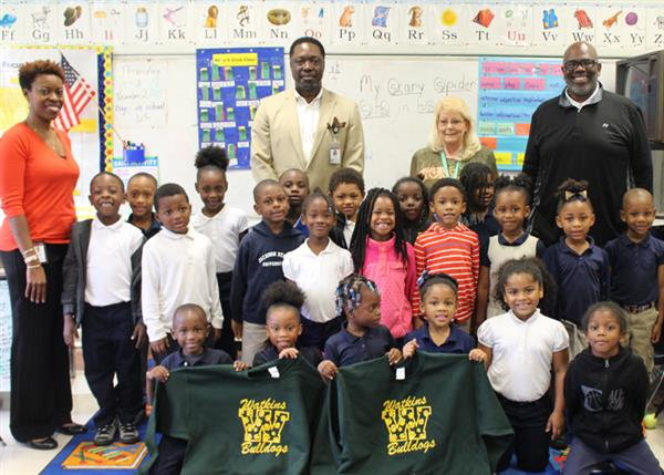 Representatives from Agape North and Watkins with students holding their new shirts