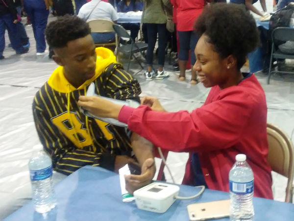 A students takes another student's blood pressure.