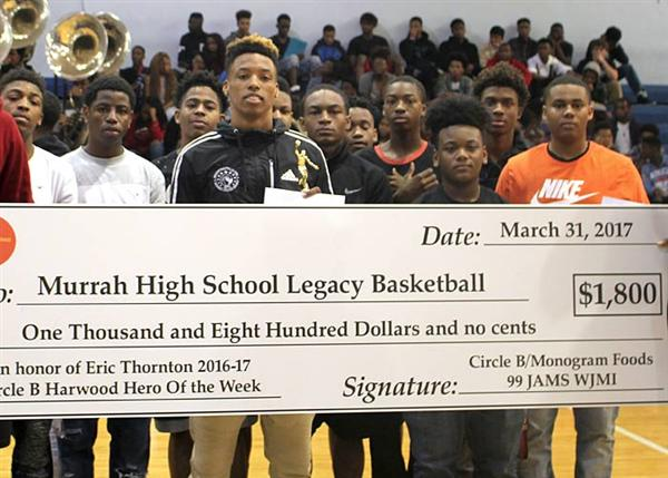 99 JAMS WJMI radio personalities present a check to the Murrah High School basketball program durin