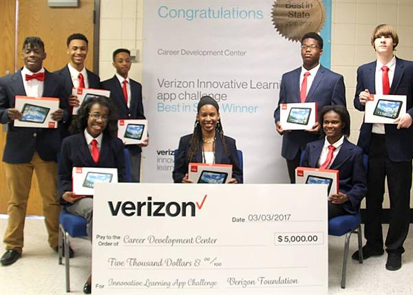 Myesha Wallace and her students proudly display tablet devices and a $5,000 presentation check they
