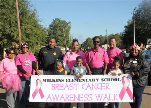 Wilkins walkers, including law enforcement officer and school staff, standing behind banner