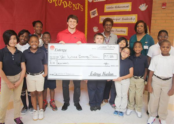 Entergy representatives, Van Winkle educators and students holding presentation check
