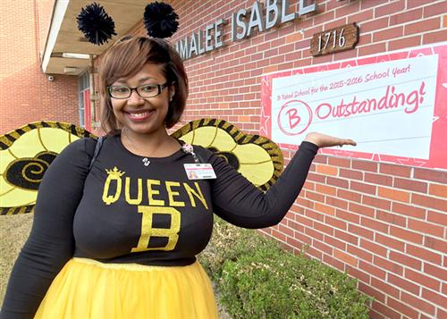Dr. Micca Knox dressed in a bee costume with B Oustanding banner hanging in the background.