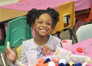 Smiling pre-k girl playing with clothes pins and colorful balls