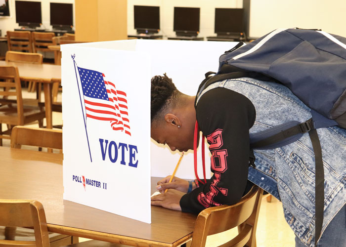 Student writing in choices on ballot