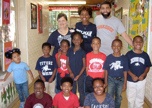 Principal, First Lady, Mayor and students wearing college shirts