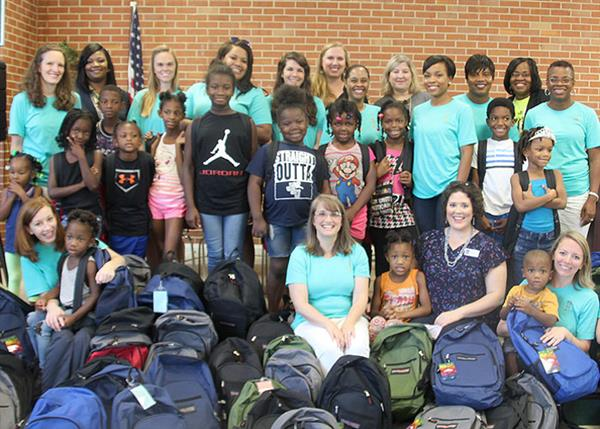 Junior League volunteers and Clausell students with about 100 backpacks