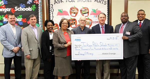 Food service director Mary Hill and Dr. Freddrick Murray with Entergy representatives holding presentation check