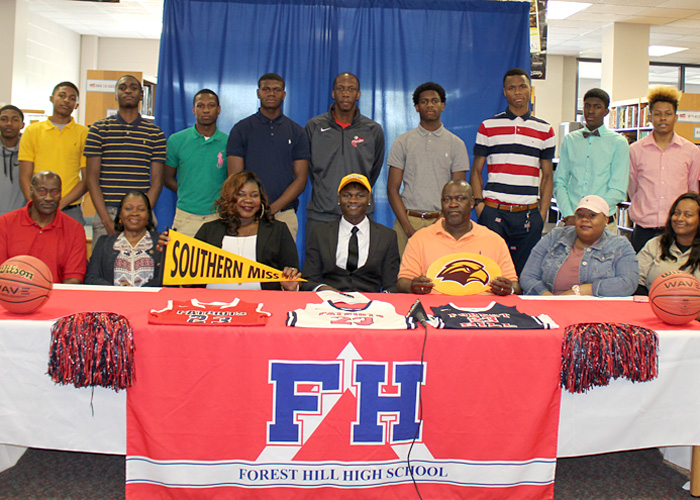 Ladarius Marshall, family, team members, at signing table