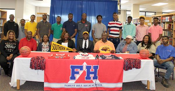 Ladarius Marshall at signing table surrounded by family and team mates