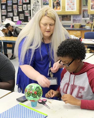 Renna Moore assists a student with an ornament