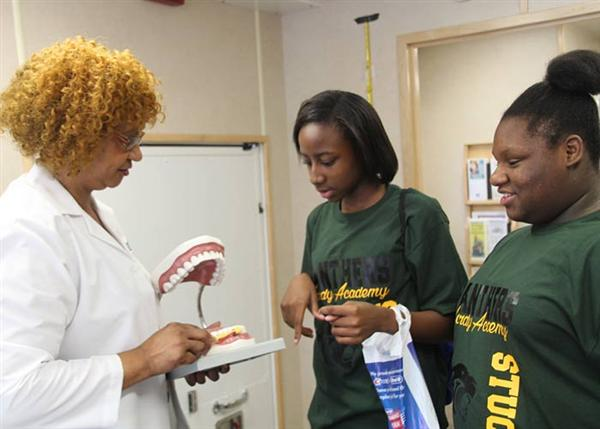 Dental instructor shows proper teeth brushing as two girls watch