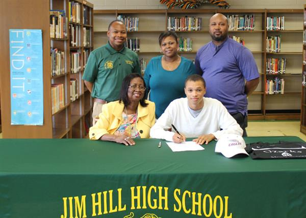 Jonathan Smith signing letter with family and coach