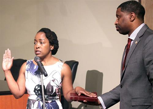 Letitia Johnson with husband Derrick Johnson who holds Bible as she takes oath