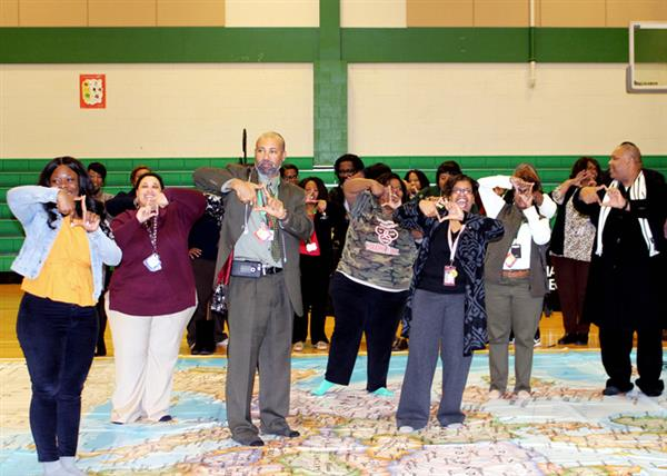 Educators smiling, attentive standing on various positions on floor map