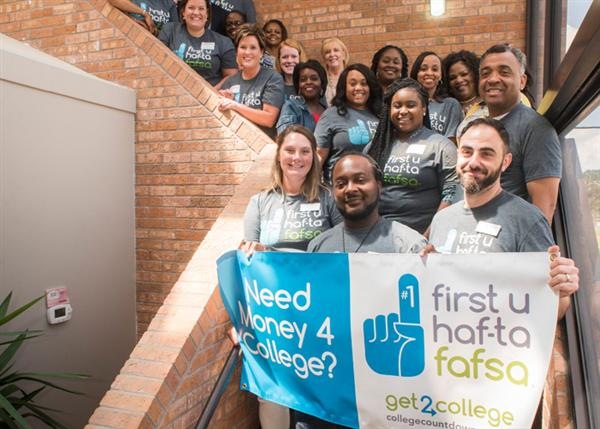 FAFSA partners and JPS high school counselors with 'First U Hafta FAFSA' banner