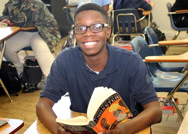 Smiling male student with book