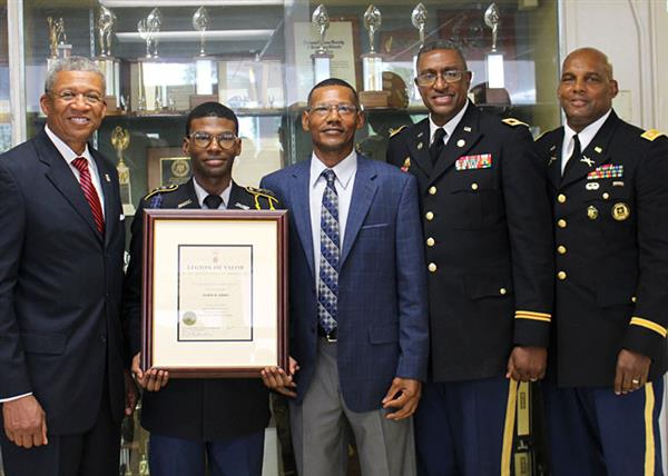 Cadet Banks holding award with presenter, parent, and instructors