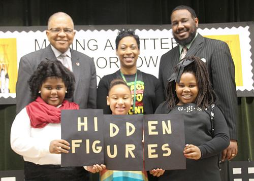 Ronnie Crudup, Principal Dionne Woody, girls as historical black women holding Hidden Figures sign