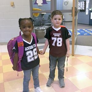 Elementary school students holding hands one wearing Jackson State and Mississippi State T-shirts