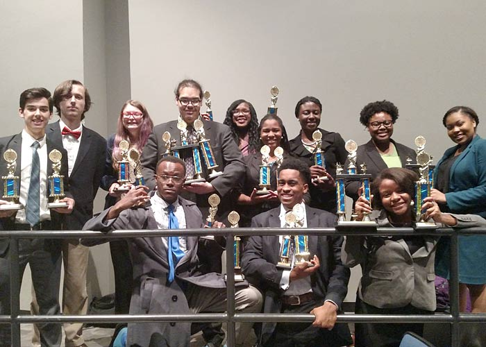 12 Murrah Speech and Debate Team members with trophies