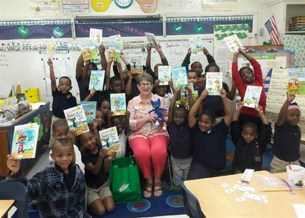 Marilyn Williams holding Pete the Cat doll surrounded by students holding their Pete the Cat books