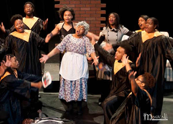 Girl actor in costume as older woman, other actors in choir robes and dress clothes, singing, and one acting dead