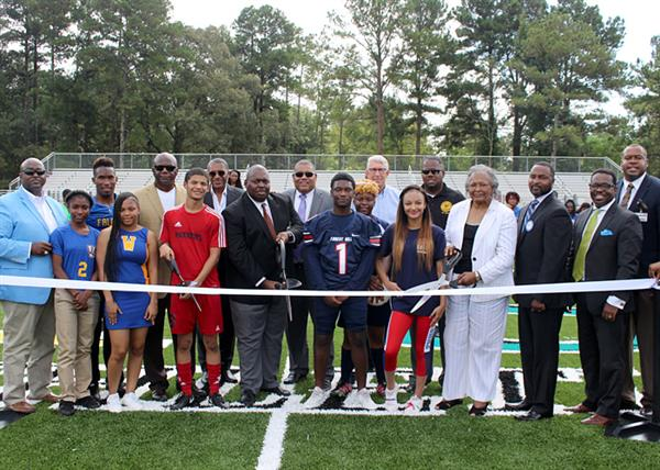 Officials and student athletes cutting ribbon