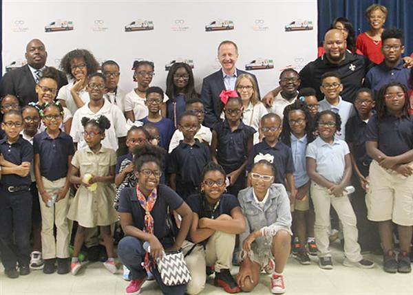 Interim superintendent pictured with sponsors and group of scholars with eyeglasses