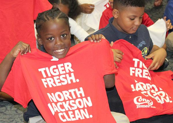 Students hold up T-shirts that read: Tiger Fresh. North Jackson Clean.