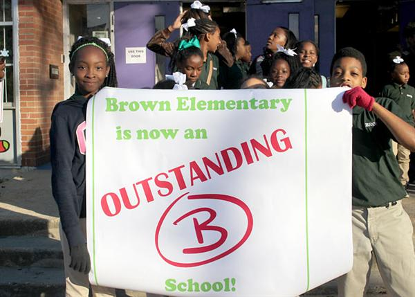 Scholars holding banner that reads Brown Elementary is now an Outstanding B School!