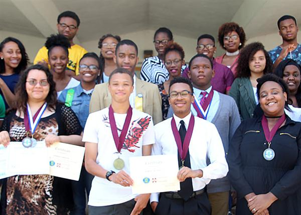 Smiling science fair winners wearing medals holding certificates