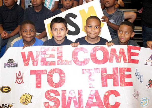 Boy students holding Welcome to the SWAC banner