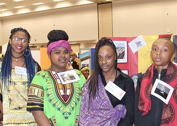 Brinkley students dressed in colorful African style fabrics  with MCEE president