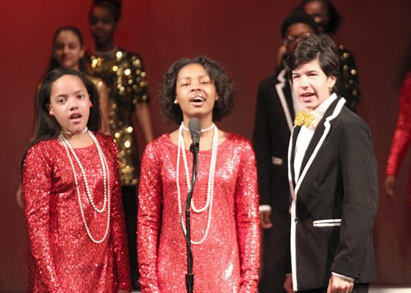 Boy in tux and girls in glitter dresses singing
