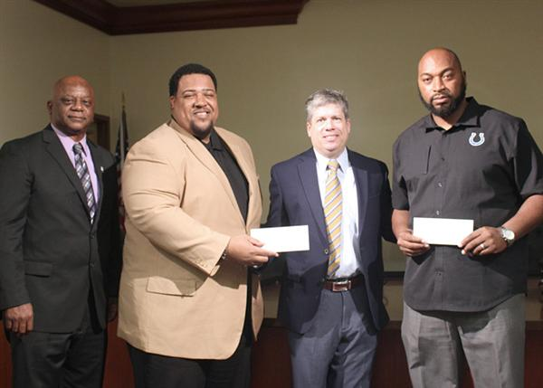 Clinton Johnson with Otis Ridley and Zackare Grady as they accept checks from Steve Jent