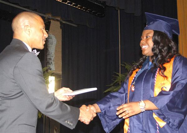 Dr. Gray congratulates a Callaway graduate in blue and orange cap and gown